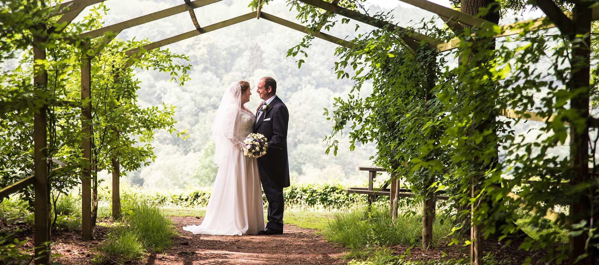 Bride and groom under laburnum arch at Arley Arboretum